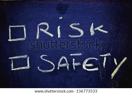 chalk writings on blackboard, choice between risk and safety - stock photo