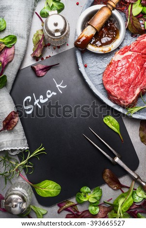Chalkboard cooking background with raw steak, meat fork,fresh seasoning and marinate, top view, place for text. Meat preparation for grill or BBQ - stock photo