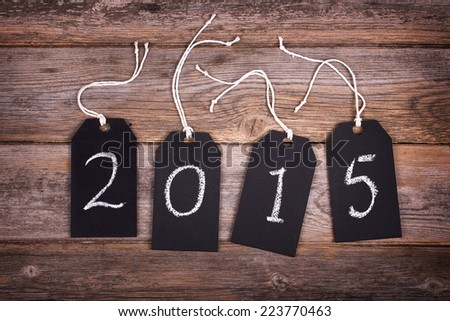 Chalkboard gift tags with strings, over old wood background, 2015 written in white chalk. New Year 2015 concept.  - stock photo
