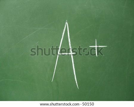 Chalkboard with A+ score written on it. - stock photo