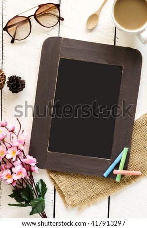 Chalkboard with cup of coffee and flower on white wooden table and copy space - stock photo