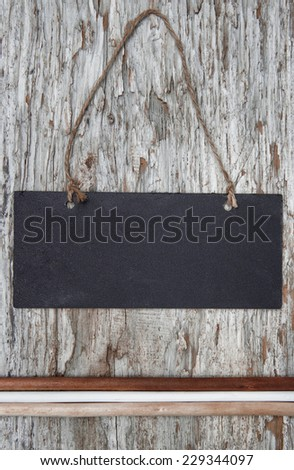 Chalkboard with dry branches on old wood background - stock photo