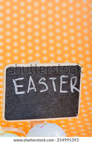 Chalkboard with Easter eggs over orange floral background - stock photo