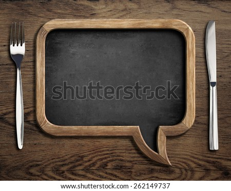 chalkboard with fork and knife on wooden dinning table - stock photo