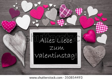 Chalkboard With German Text Alles Liebe Zum Valentinstag Means Happy Valentines Day. Many Pink Textile Hearts. Wooden Background With Vintage, Rustic Or Retro Style. Black And White Image. - stock photo