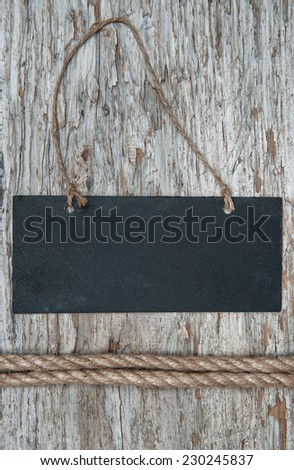 Chalkboard with rope on the old wood background - stock photo