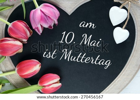 Chalkboard with the german words On May 10 is Mothers Day / Mothers Day - stock photo