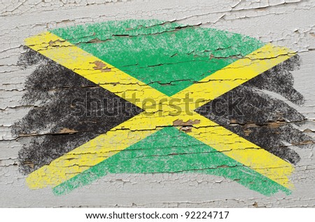 Chalky jamaican flag painted with color chalk on grunge wooden texture - stock photo