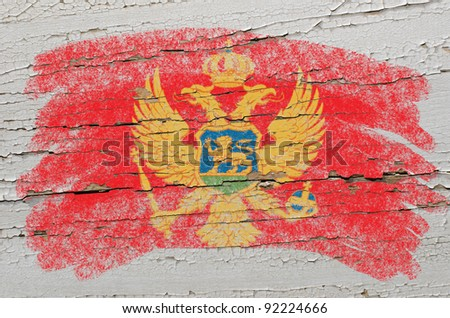 Chalky  montenegrian flag painted with color chalk on grunge wooden texture - stock photo