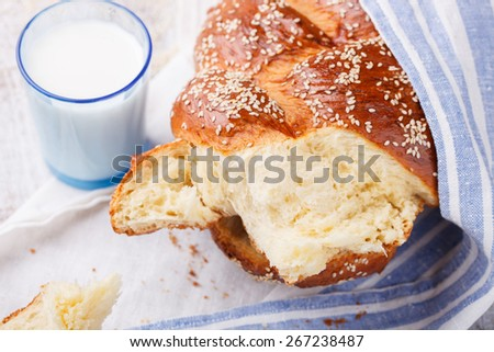 Challah bread with sesame seeds and a glass of milk, pastry.selective focus - stock photo