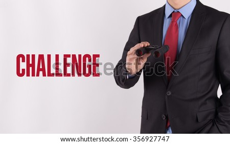 CHALLENGE text on white background with businessman holding binoculars - stock photo
