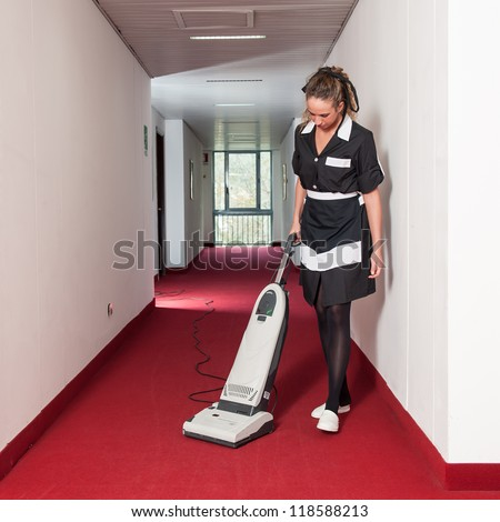 Chambermaid woman cleaning in a hotel with vacuum cleaner. - stock photo
