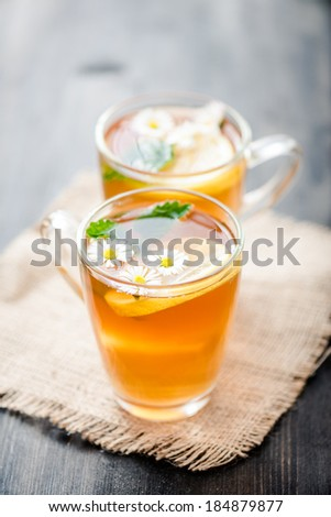 chamomile tea in a glass cup on wooden background - stock photo