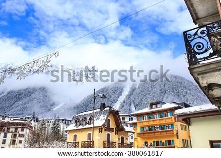 Chamonix town with snowy mountains on the background. Chamonix-Mont-Blanc was the site of the first Winter Olympics in 1924 and it's one of the oldest ski resorts in France. - stock photo
