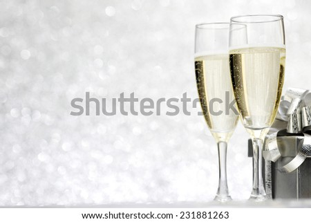 Champagne and present on silver bokeh background - stock photo