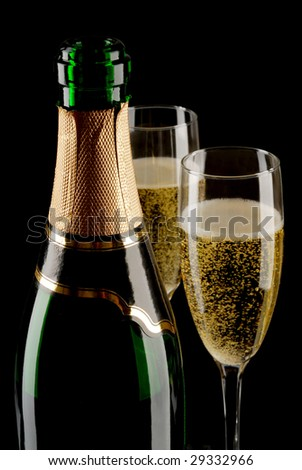 Champagne bottle and two flutes (glasses) on black background - stock photo
