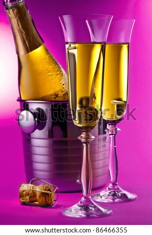 Champagne bottle in cooler and two champagne glasses. Isolated on a pink background. - stock photo