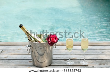 Champagne bottle in ice bucket with flower and champagne glass by swimming pool - stock photo