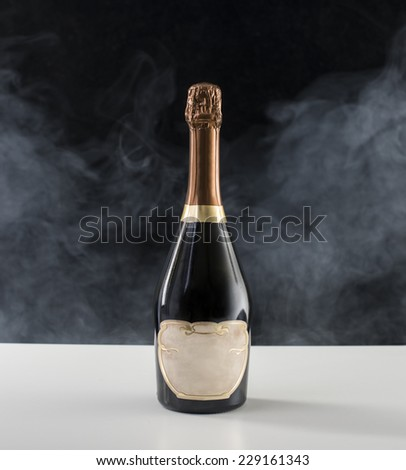 Champagne bottle, on a black background, with smoke behind the bottle. - stock photo