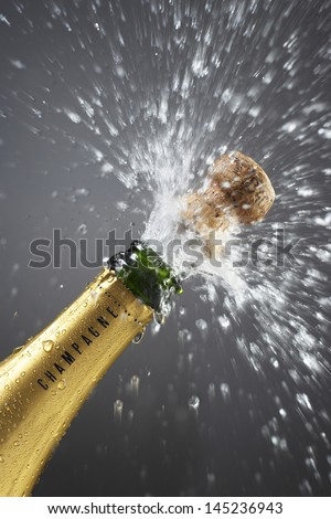 Champagne bottle popping cork close-up - stock photo