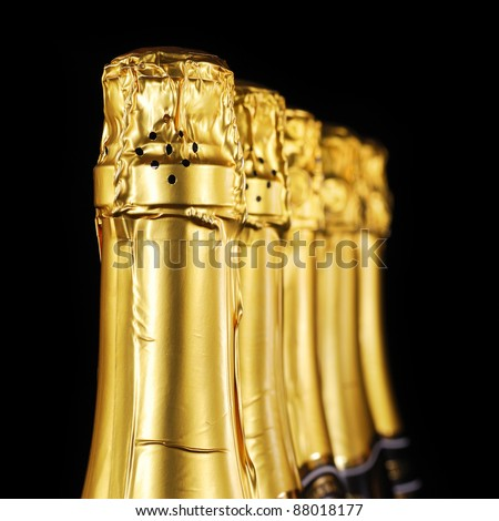 Champagne bottles in gold foil - stock photo
