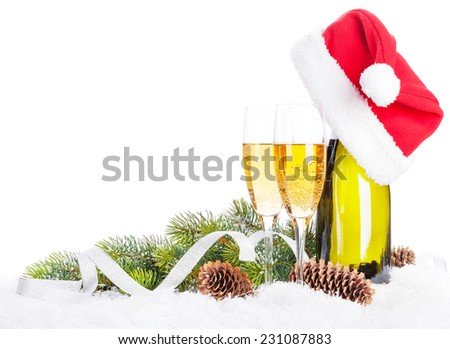 Champagne, christmas decor and santa hat over snow and fir tree with copy space - stock photo