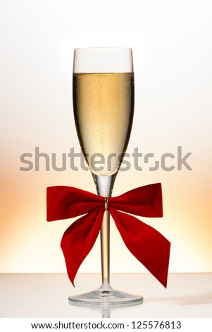 Champagne flute with red ribbon bow - stock photo