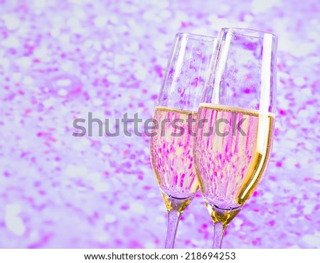 champagne flutes with gold bubbles on blur violet tint light background love concept - stock photo