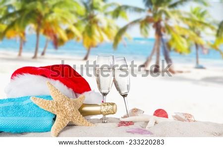 Champagne flutes with santa cap on sunny beach, celebration theme. - stock photo