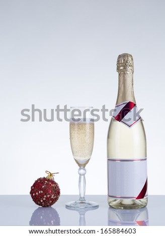 Champagne glass, bottle, and New Year decoration, studio shot on grey background  - stock photo