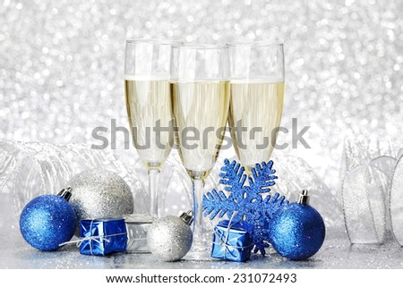 Champagne glasses and new year decoration on silver bokeh background - stock photo