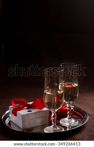 Champagne glasses, gift and  hearts for celebrating Valentines Day or wedding, selective focus - stock photo