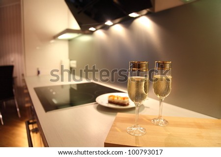 Champagne glasses in beautiful modern kitchen - stock photo