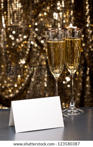 Champagne glasses in front of gold glitter background - stock photo
