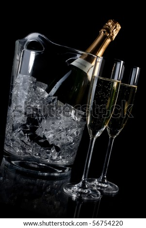 Champagne in a ice bucket and two champagne flutes - stock photo