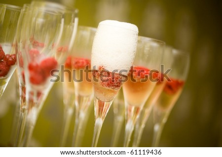 Champagne in glasses with fresh red raspberries - stock photo