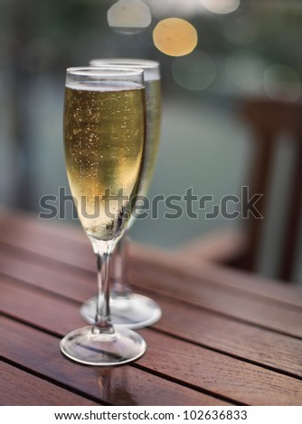 Champagne in the glasses on the table in the evening - stock photo