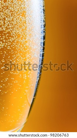 champagne in wineglass on a yellow background. - stock photo