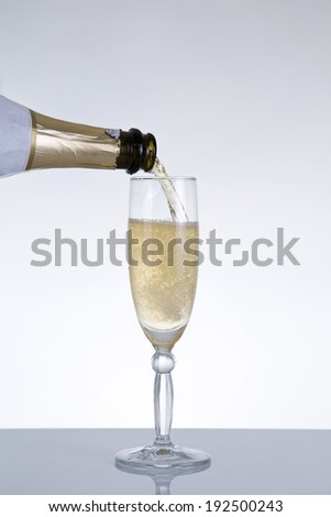 Champagne pouring into a glass, natural reflection, studio shot on grey background  - stock photo