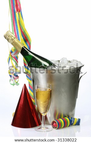 Champagne toast composition with streamers, hat and glass on bright background - stock photo