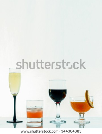 Champagne, whiskey, cocktail, wine in glasses next to a white background - stock photo