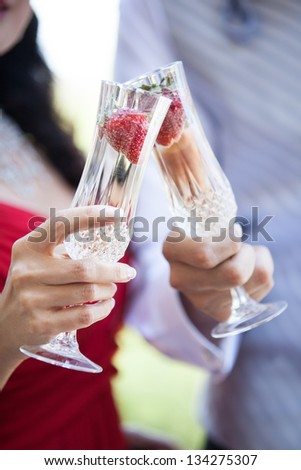 Champagne with strawberries in the forefront of a romantic couple toasting - stock photo