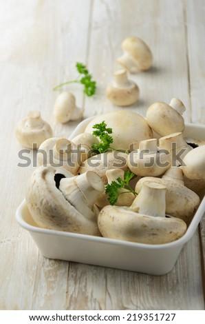 Champignon mushrooms on white wood background - stock photo