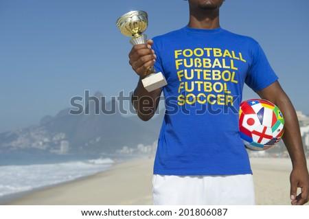 Champion Brazilian football player holding trophy and soccer ball in international football t-shirt Ipanema Beach Rio de Janeiro Brazil - stock photo