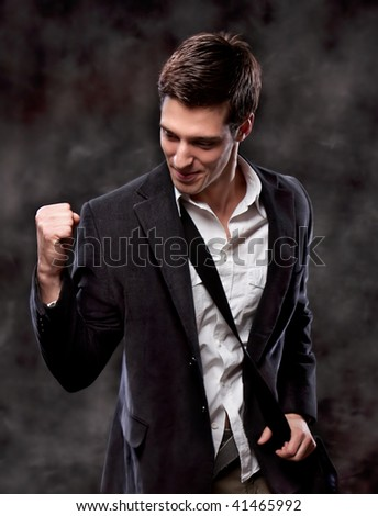 Champion business man standing with fists clenched in victory. Studio shot - stock photo