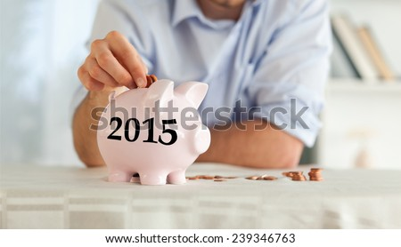 Change being put into piggy bank against 2015 in grey - stock photo