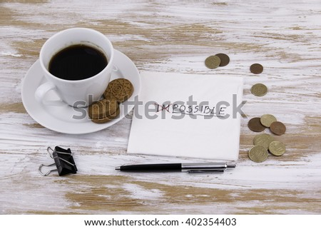 Change impossible to possible. Handwriting on a napkin with a cup of coffee