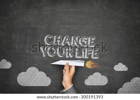 Change your life concept on black blackboard with businessman hand holding paper plane - stock photo
