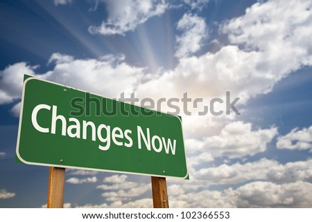 Changes Now Green Road Sign with Dramatic Clouds, Sun Rays and Sky. - stock photo