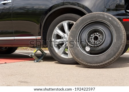 Changing the wheel on a car with the vehicle jacked up on a hydraulic jack and the spare wheel propped up against the front side of the car close up view - stock photo